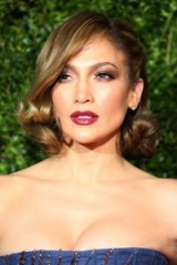 Jennifer Lopez with a glamorous curled bob, tucked behind one ear. Celebrity hairstyles | dramatic eye make up | dark red lips
