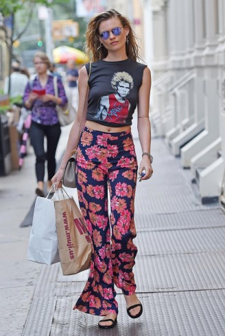 Model Behati Prinsloo does chic rock chick so well in a sleeveless graphic crop tee and floral print pants. models off duty – celebrity street style