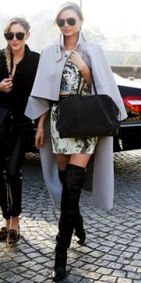 Model Miranda Kerr in a long pale grey cape, black leather over the knee boots & Aviators. Celebrity fashion – style icons