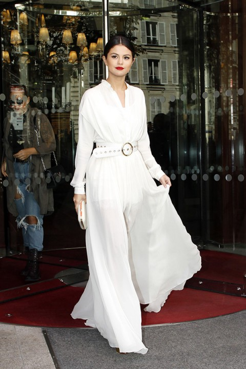 Selena Gomez left her hotel in Paris looking cool & sophisticated, wearing a white belted semi sheer maxi dress, with long sleeves & flowing skirt, 26 September 2015. Celebrity chic style / long dresses
