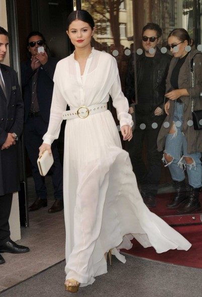 Star style ~ Selena Gomez looked chic leaving her hotel in Paris, wearing a white belted semi sheer maxi dress, with long sleeves & flowing skirt, 26 September 2015. Celebrity fashion / long dresses