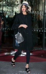 Selena Gomez street style…black loose fitting coat with frill sleeves, a pair of black leggings, Kurt Geiger KROW mules kurtgeiger.com, a Maison Michel wide brim hat and carrying a metallic clutch. Celebrity fashion | star style | chic looks | what celebrities wear