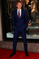 "Actor Tom Hiddleston wearing a navy suit and purple tie, attends the Bergdorf Goodman ""Crimson Peak"" inspired window unveiling at Bergdorf Goodman, New York City, 13 October 2015. Celebrity style – mens suits – actors on the red carpet – events"