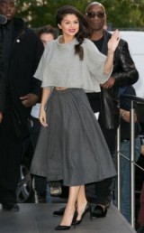 Selena Gomez in a pale grey oversized cropped sweater, dark grey A-line skirt and black pointy pumps. Celebrity fashion | star style | chic looks | outfits