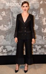 Lily Collins looked chic in black Chanel trouser suit with cropped wide leg pants, when she attended the Chanel Mademoiselle Prive Exhibition launch party, Saatchi Gallery, London, October 2015. Celebrity fashion – designer outfits – stylish looks – celebrities at events