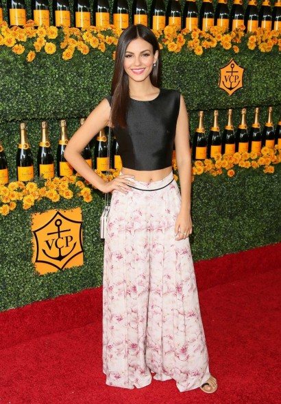 Victoria Justice wearing a black crop top and wide leg floral trousers, attends the Sixth-Annual Veuve Clicquot Polo Classic at Will Rogers State Historic Park on 17 October 2015, Pacific Palisades, California. Celebrity fashion | star style | celebrities at events | outfits