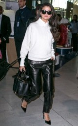 Luxe travel style from Selena Gomez at Charles-de-Gaulle airport, France…white ribbed sweater, black leather trousers, patent pointy pumps and a luxury leather tote. Celebrity fashion | star style outfits | what celebrities wear