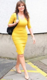 A curvy Carol Vorderman in a fitted mustard pencil dress that looks bright and cheerful!