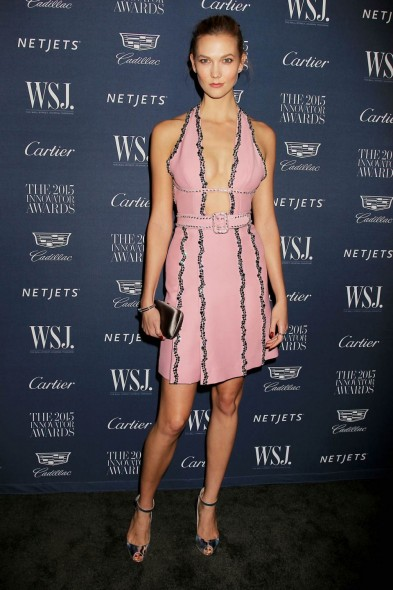Model Karlie Kloss at the WSJ Innovator Awards in NYC, wearing a plunging pink mini dress, trimmed with black stones, and a pair of silver peep toe ankle strap sandals, Nov 2015. Celebrity style / event fashion / embellished dresses