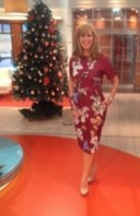 Kate Garraway posing next to the GMB Xmas tree in red floral ASOS.com dress and Next.co.uk shoes