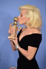 Lady Gaga wearing a black Versace gown & her hair worn in platinum Marilyn Monroe style waves, kisses her Golden Globe award for best actress in a mini series at the 2016 Golden Globes – celebrity style – awards – events