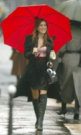 Carrie Bradshaw style ~ walking in the rain wearing a pink embellished bustier, above the knee gathered skirt, knee high leather boots, black trench and carrying a large cream vintage clutch and bright red umbrella. SATC fashion ~ Sex and the City outfits ~ SJP
