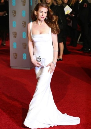 Isla Fisher channels old Hollywood glamour at the BAFTAs, dressed in a white Stella McCartney gown, and wearing her long hair swept to the side, styled in vintage waves. Celebrity fashion | star style | BAFTA Awards dresses | red carpet gowns - flipped