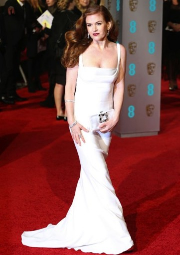 Isla Fisher channels old Hollywood glamour at the BAFTAs, dressed in a white Stella McCartney gown, and wearing her long hair swept to the side, styled in vintage waves. Celebrity fashion | star style | BAFTA Awards dresses | red carpet gowns