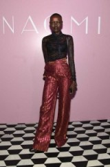 Model Grace Bol dressed in pink metallic wide leg trousers & a black sheer lace blouse, attends the launch of Naomi hosted by Marc Jacobs and Benedikt Taschen at the Diamond Horseshoe in New York, April 2016. Models at events – red carpet style outfits