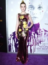 A very elegant and confident looking Elle Fanning wears a purple sequined Dolce & Gabbana floor length gown to the L.A. premiere of the haunting film The Neon Demon