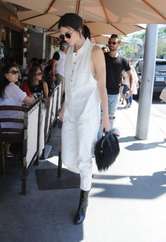 Kendall Jenner out in Beverly Hills wearing a white sleeveless loose fitting jumpsuit and black patent calf length boots. Celebrity street style | models off duty | casual star style | jumpsuits | outfits - flipped