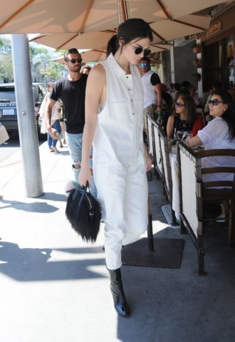 Kendall Jenner out in Beverly Hills wearing a white sleeveless loose fitting jumpsuit and black patent calf length boots. Celebrity street style | models off duty | casual star style | jumpsuits | outfits