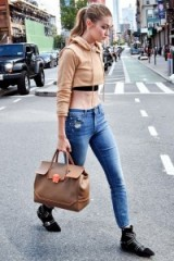 Gigi Hadid out in New York…camel cropped hoodie, distressed skinny jeans, black studded ankle boots and a light brown leather holdall. Casual celebrity fashion | star style outfits | street style USA | models off duty