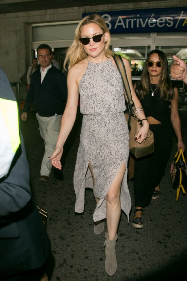 Kate Hudson travel style wearing a grey alter dress with front slits and suede ankle boots