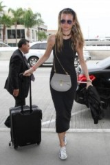 Model Bhati Prinsloo looks so stylish in a simple black tank dress, grey Chloe Drew bag and a pair of silver metallic sneakers – celebrity travel style – models outfits