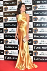 Amal glamour……stunning in a sleeveless gold metallic gown with floral corsage at the neckline