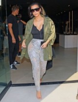 Kim Kardashian looking sensational in a black low cut bodysuit, khaki green jacket and a pair of Balmain sparkling silver semi sheer trousers. Kardashian's fashion | celebrity outfits | star style glamour