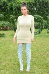 Kim Kardashian wore a beige ribbed mini dress and thigh high distressed denim boots to the 'Revolve in the Hamptons party' in July 2016. Kardashians fashion | star style outfits | celebrity dresses