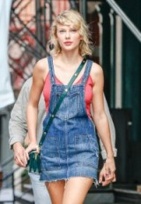 Taylor Swift street style out in New York City…strappy red vest, blue denim pinafore dress and a dark green crossbody bag. Casual celebrity dresses | star style fashion