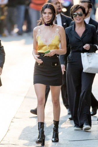 Kendall Jenner street style…yellow lace trim camisole, black mini skirt, patent calf length boots and wide choker necklace. Celebrity fashion | star style outfits | outfit inspiration | cami tops | on trend looks