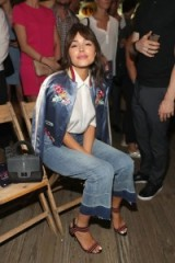 Olivia Culpo at Tommy Hilfiger in a blue satin bomber jacket, white shirt and jeans – front row celebrities at New York Fashion Week Spring 2017. Celebrity fashion | star style outfits