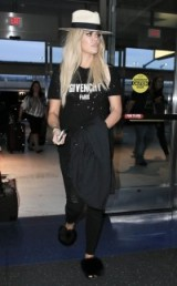 Khloe Kardashian keeps it casual at NYC airport in a Givenchy tee, ripped skinnies, fluffy slippers and fedora hat – celebrity travel style – cool style outfits