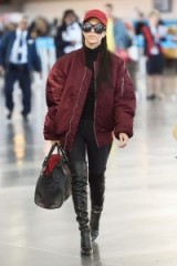 Kourtney Kardashian oversized burgundy bomber jacket, black leather over the knee boots and red cap. Casual celebrity fashion | star style jackets