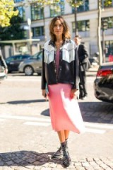 Alexa Chung wears a pink midi dress, black leather western jacket, with white fringe detail, and lace up ankle boots in Paris for fashion week SS17