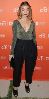 Sarah Hyland dressed in a shimmering plunge front bodysuit and black high waisted trousers, with tie belt, attends the Los Angeles No Kid Hungry Dinner, Sept 2016