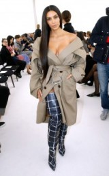 Kim Kardashian dressed in a trench and thigh high boots at the Balenciaga show during Paris Fashion Week