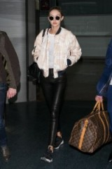 Gigi Hadid travel style…black leather skinny pants with a pink and white print bomber jacket. Celebrity outfits | models off duty | casual star style