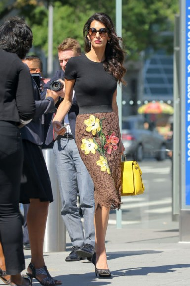 Amal Cloony's chic look wearing a black tee, a floral lace statement pencil skirt from Dolce & Gabbana and a bright yellow handbag