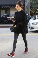 Kendall Jenner street style…oversized black sweater, skinny leather pants and a pair of black and red Nike sneakers. Models off duty | casual star style | celebrity winter outfits