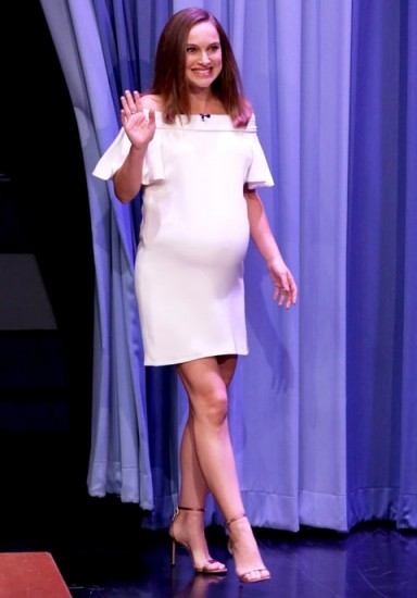 Natalie Portman's pregnancy style wearing a white off the shoulder frill sleeved shift dress. Celebrity dresses | star style fashion