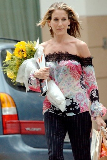 Carrie Bradshaw wearing an off the shoulder top with pinstripe pants & carrying flowers and an edition of Vogue magazine…perfect! - flipped