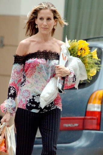 Carrie Bradshaw wearing an off the shoulder top with pinstripe pants & carrying flowers and an edition of Vogue magazine…perfect!