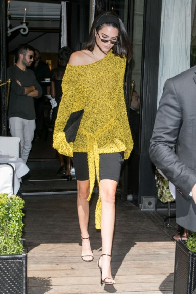 Kendall Jenner's chic Paris style dressed in a yellow knitted oversized belted top, worn off one shoulder, a black skirt and barely there sandals