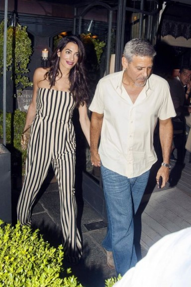 Amal in Italy with husband George, dressed in a strapless stripe jumpsuit, August 2017