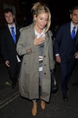 Sienna Miller leaving the Apollo Theatre wearing a Burberry trench over a graphic t-shirt and jeans.