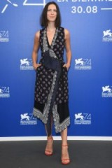 Rebecca Hall looked stylish in a sleeveless asymmetric printed dress by Altuzarra and a pair of red strappy sandals, attending a photocall at the 2017 Venice Film Festival.