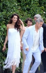 Amal Clooney at Lake Como dressed in a white layered fringed slip dress