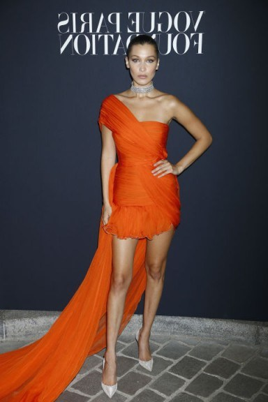 Bella Hadid back in July 2017, wearing a bright orange, one-shoulder draped mini dress with an extra long train, from the Giambattista Valli Spring 2017 Couture collection, attending the Vogue Foundation Dinner 2017. - flipped