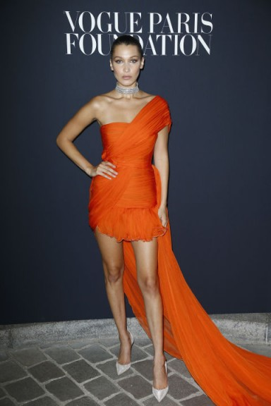 Bella Hadid back in July 2017, wearing a bright orange, one-shoulder draped mini dress with an extra long train, from the Giambattista Valli Spring 2017 Couture collection, attending the Vogue Foundation Dinner 2017.