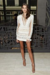 Kaia Gerber in a white ruffled mini dress and silver barely there sandals / stylish looks